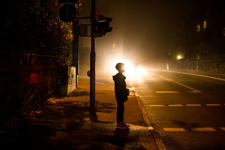 Boy standing on illuminated street at night