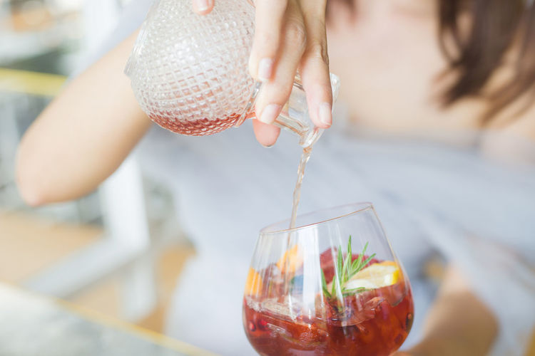 Midsection of woman pouring drink in glass