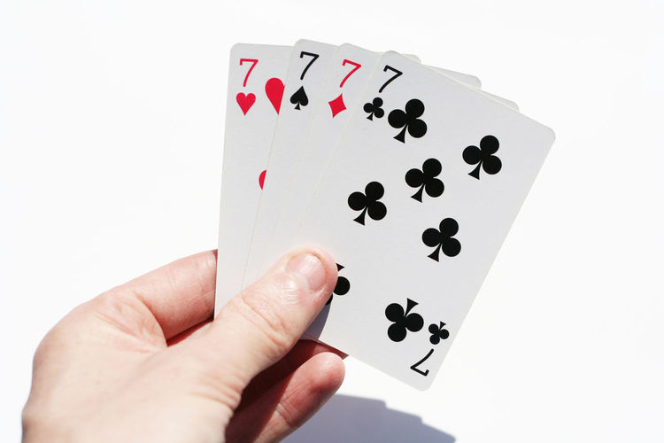 Close-up of hand holding playing cards over white background