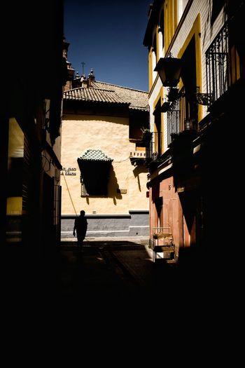 Silhouette people walking on street by building against sky