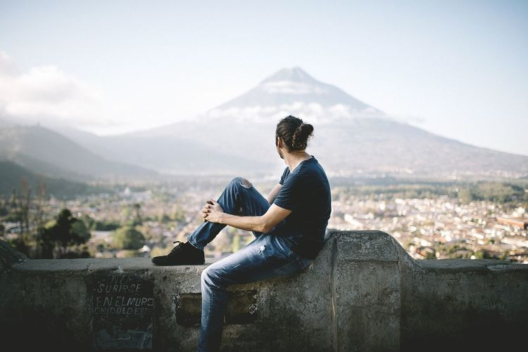 Side view of young man sitting on retaining wall against mountain
