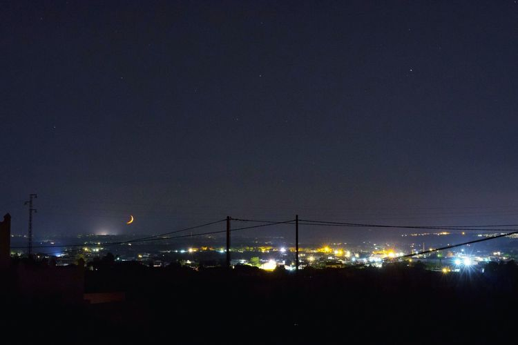 Low angle view of silhouette lights against clear sky at night