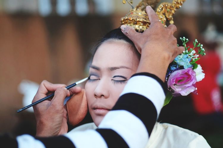 Cropped image of artist applying make-up on young woman