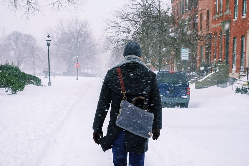 Blizzard City Cold Cold Temperature Covered Covering Day Emergency Frozen Full Length Man Walking Neighborhood One Person Outdoors Recreational Pursuit Season  Snow Warm Clothing Weather White White Color Winter