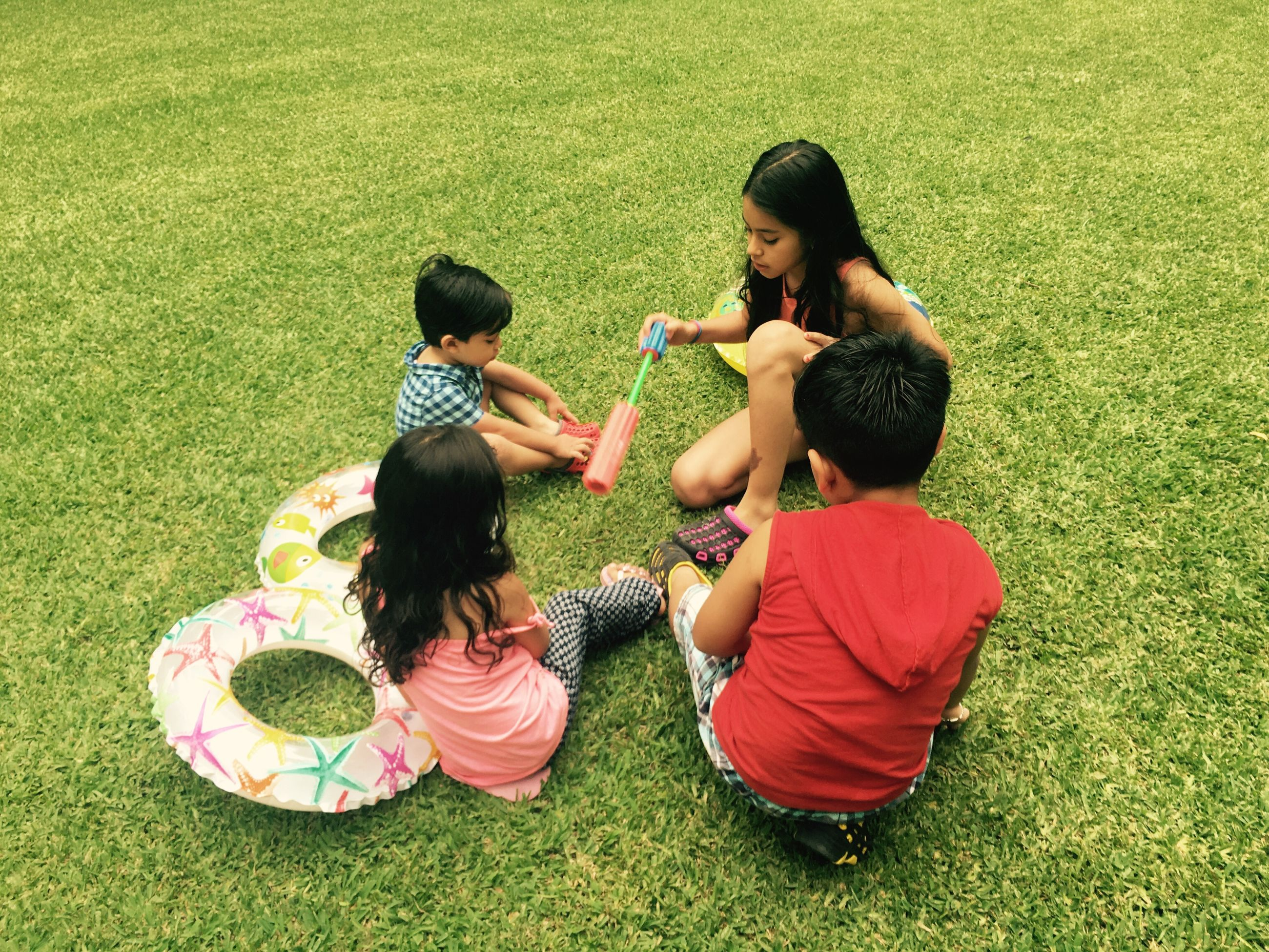 child, two people, high angle view, directly above, family, childhood, grass, girls, full length, fun, females, brother, playing, outdoors, people, togetherness, heat - temperature, friendship, day, human body part, adult