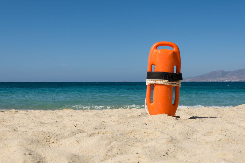 Orange rescue buoy on the beach Aid Baywatch Emergency Life Rescue Can Swimming Travel Vacations Assistance Bay Beach Buoy Coast Danger Duty Equipment Gear Lifeguard  Orange Color Protection Rescue Safety Sea Security Tropical Climate