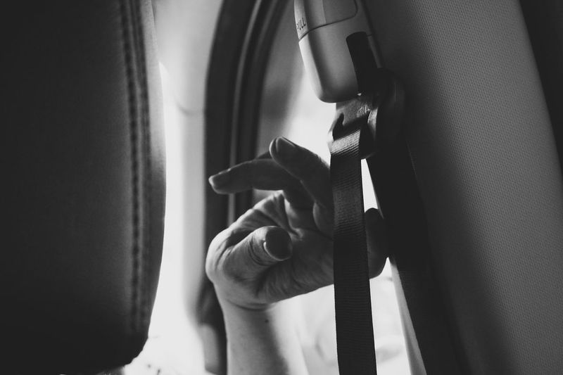 Cropped image of person touching seat belt