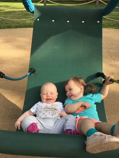 Cute siblings resting in hammock at park