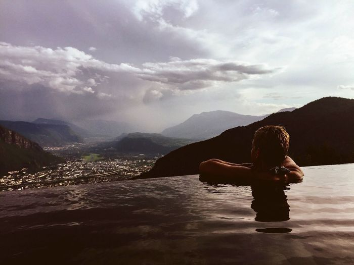 Woman relaxing in infinity pool by mountains against sky