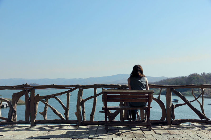 Rear view of woman sitting on railing against clear sky