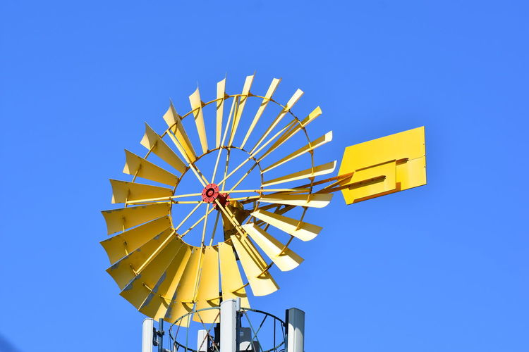 Low angle view of water wheel against clear blue sky