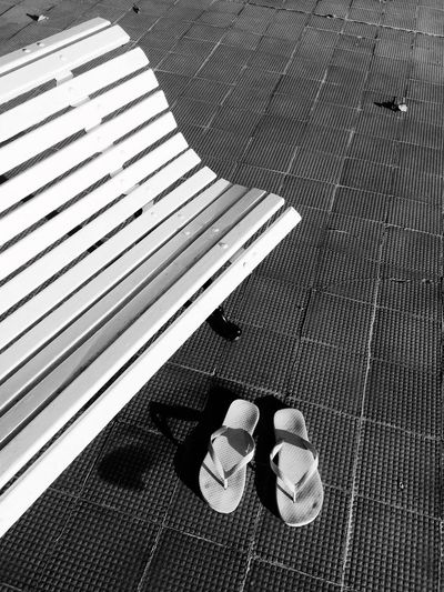 High angle view of flip-flops by bench