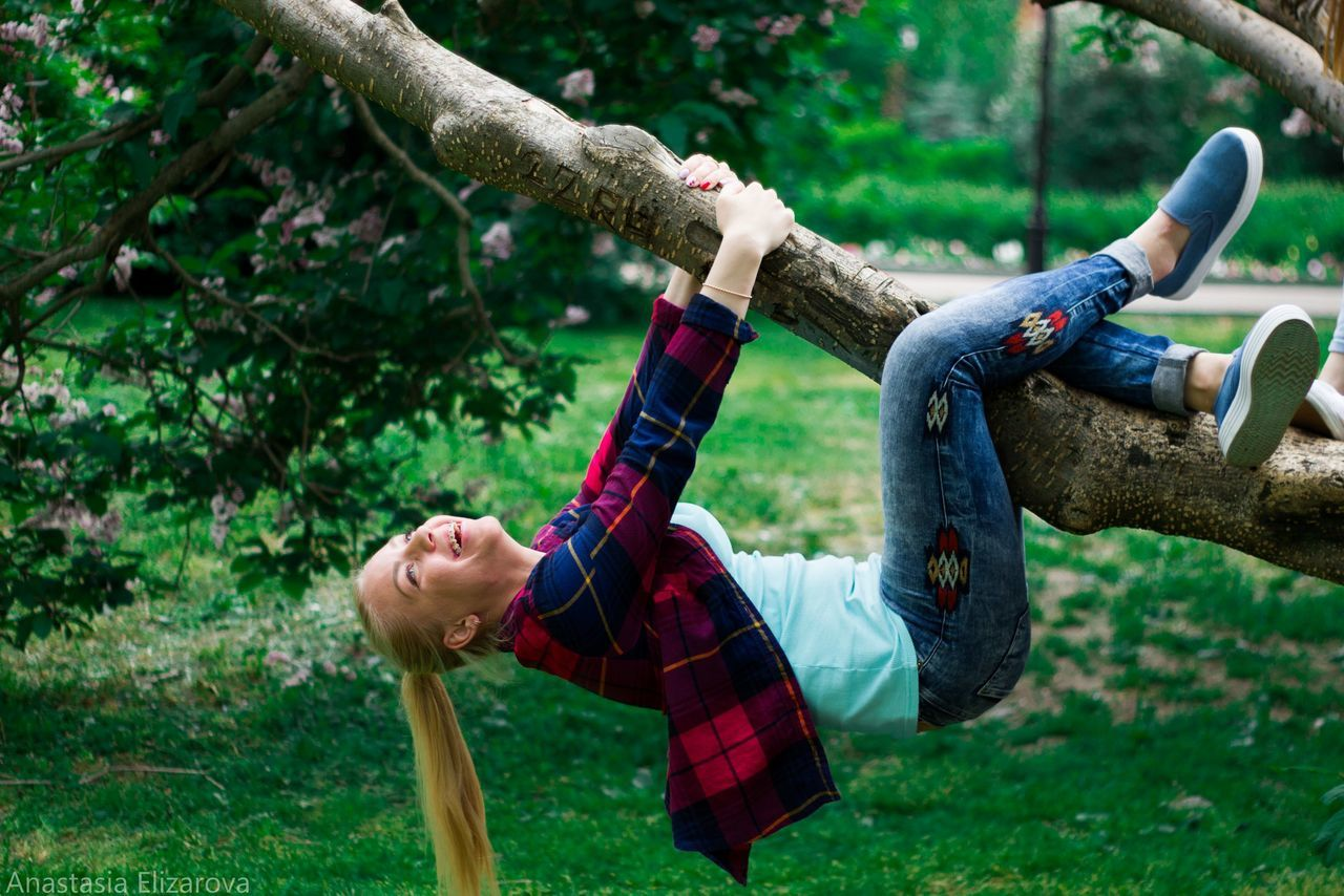 tree, day, casual clothing, tree trunk, one person, outdoors, leisure activity, young adult, real people, hanging, branch, climbing, nature, grass, young women, rope swing, axe, adults only, adult, people