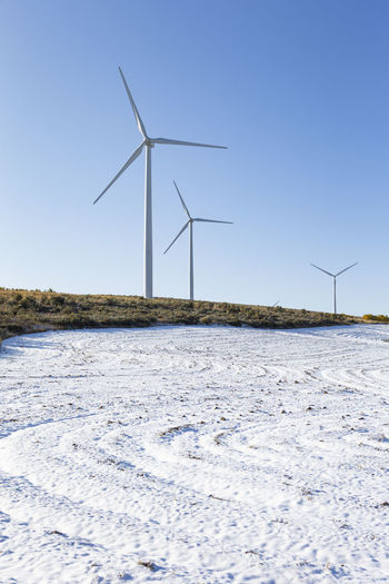 Wind turbines on snowy field against clear sky