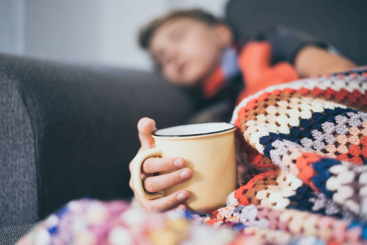 Boy holding cup while sleeping on sofa at home