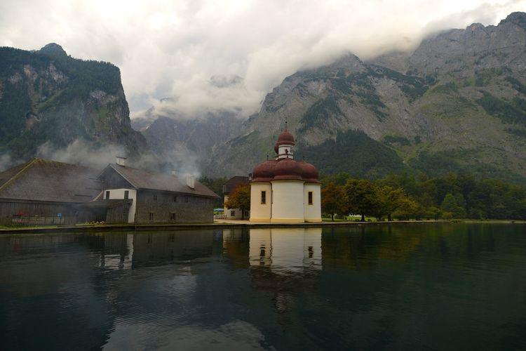 St bartholomews church by calm lake against mountain