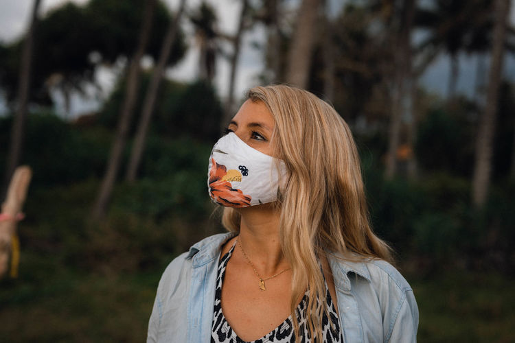 Portrait of young woman standing with mask