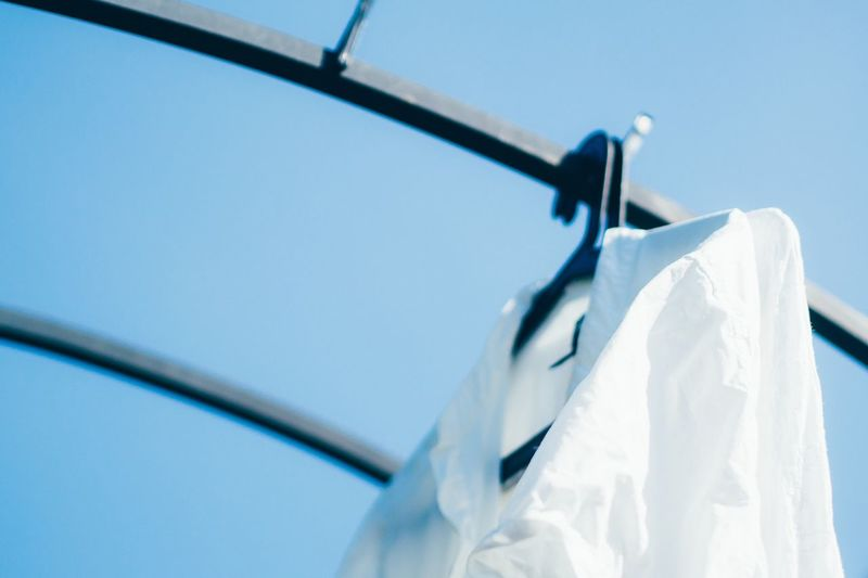Low angle view of white shirt drying on rack against clear blue sky