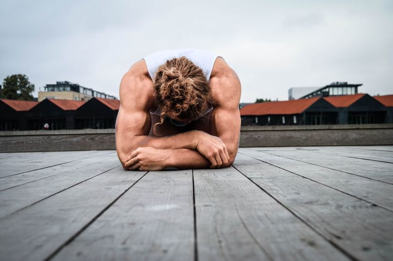 Muscular man lying on jetty by houses against sky