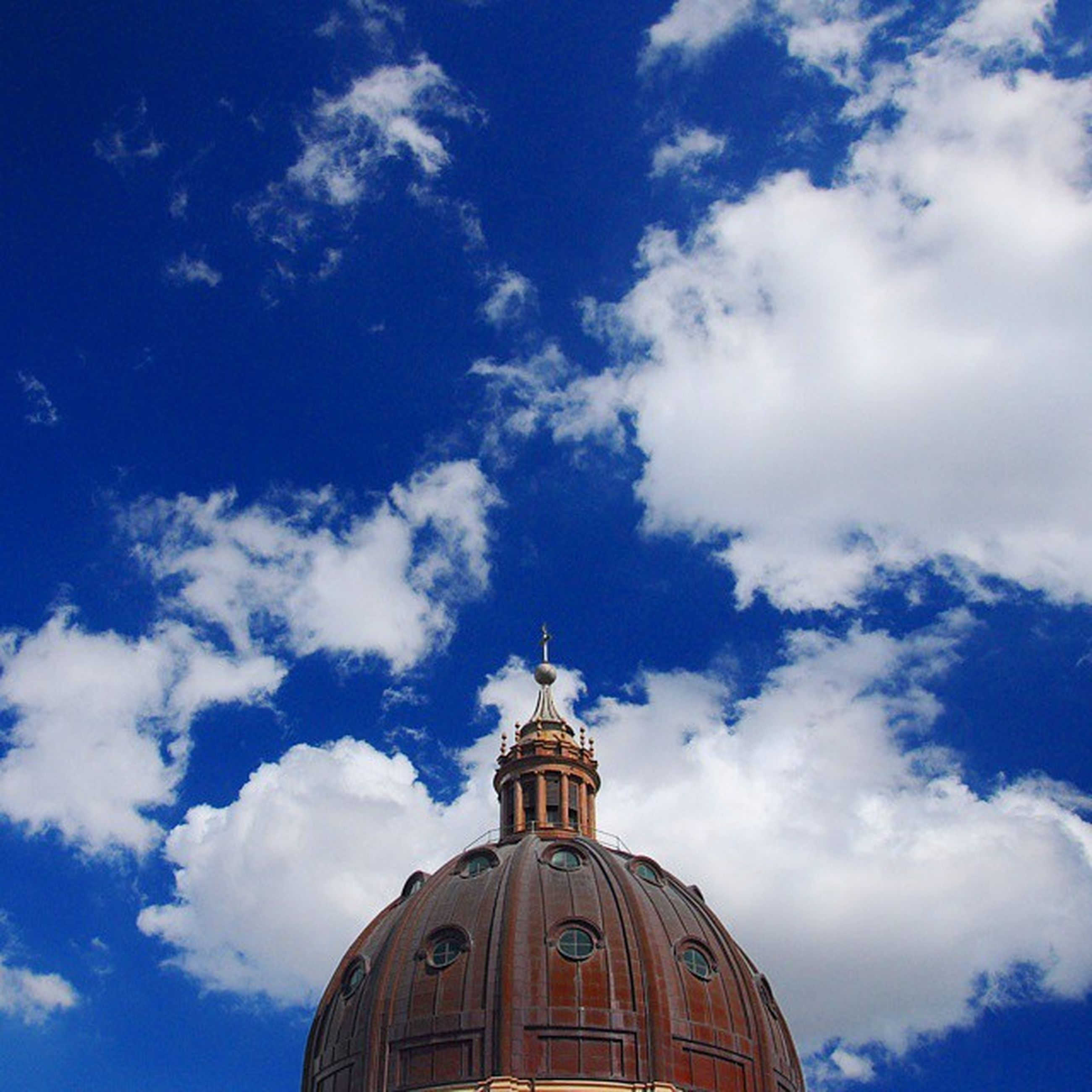 building exterior, low angle view, architecture, built structure, place of worship, church, religion, sky, dome, spirituality, high section, blue, cloud - sky, cathedral, cloud, cross, outdoors, day