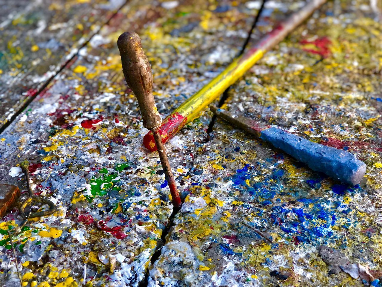 no people, close-up, high angle view, still life, wood - material, day, brush, textured, art and craft, metal, paintbrush, creativity, yellow, paint, focus on foreground, outdoors, messy, nature, multi colored, craft, art and craft equipment