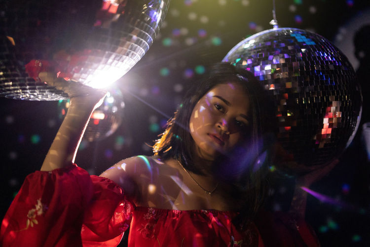 Portrait of young woman standing amid disco balls at nightclub