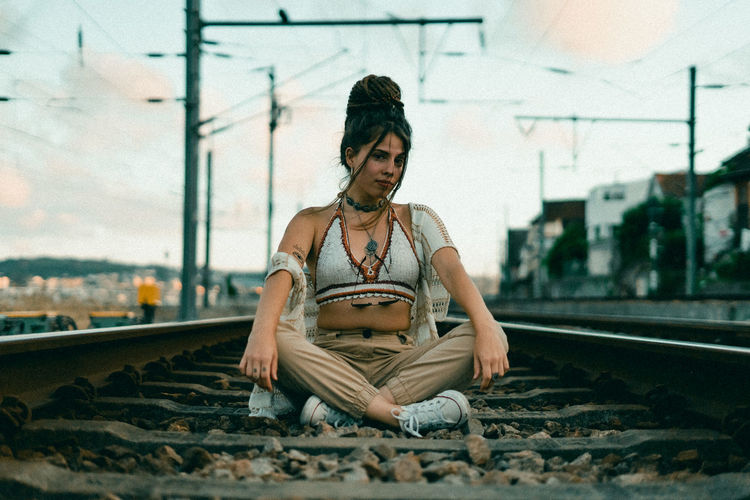 Young woman sitting on railroad track