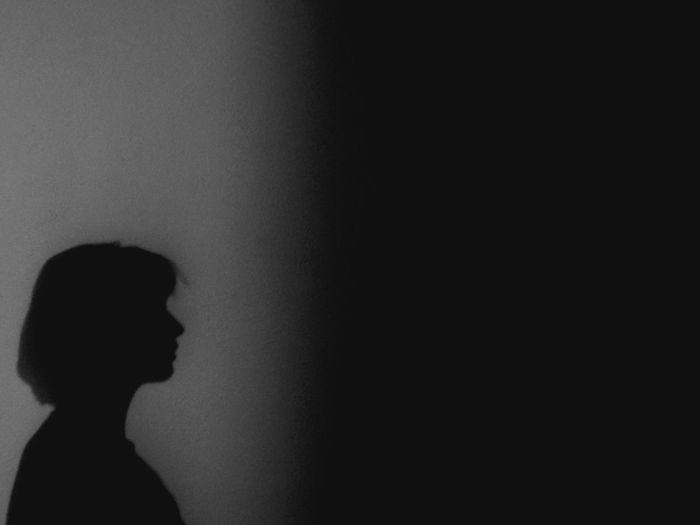 Portrait of silhouette woman against wall