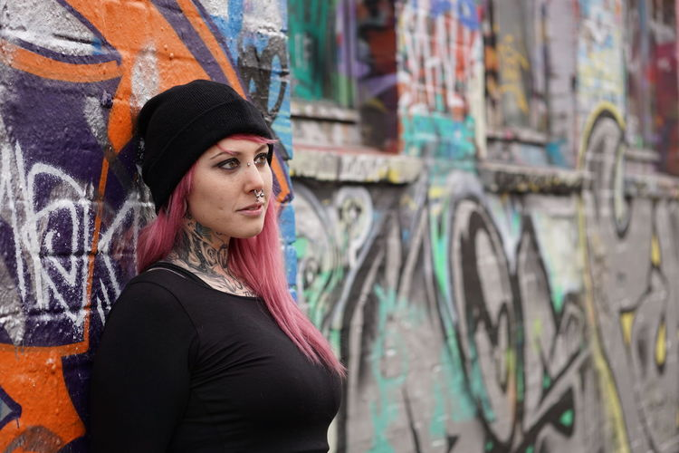 Alternative Authentic Casual Clothing Emo Girl Graffiti Inked Lifestyles Person Pierced Piercing Pink Hair Punk Real People Street Tattoo Tattooed Urban Wall Woman Young Adult Young Women Youth