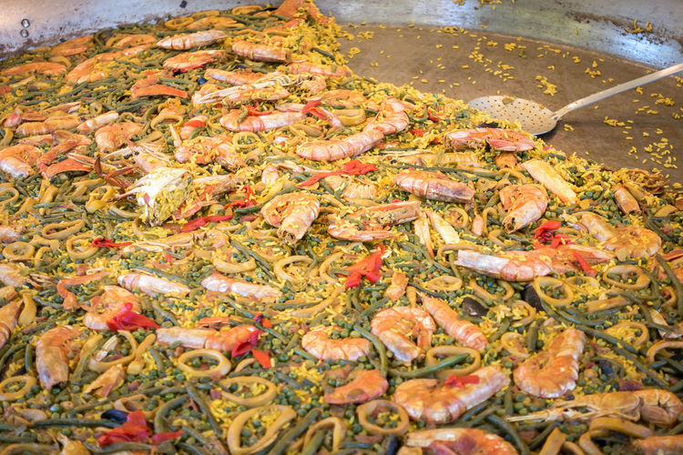 Large pan of paella in a street tray with food Food And Drink Food Seafood Kitchen Utensil Freshness Spoon High Angle View Animal No People Meat Fish Water Shrimp - Seafood Healthy Eating Crustacean Preparation  Close-up Wellbeing Preparing Food Wooden Spoon Dinner
