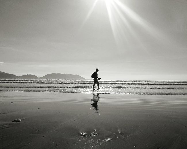 Silhouette person on shore at beach against sky