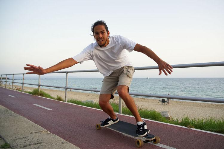 Portrait of man skateboarding on footpath against sea at sunset