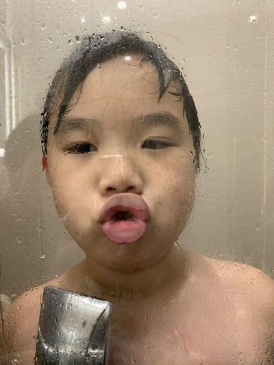 Portrait of shirtless boy drinking water in bathroom