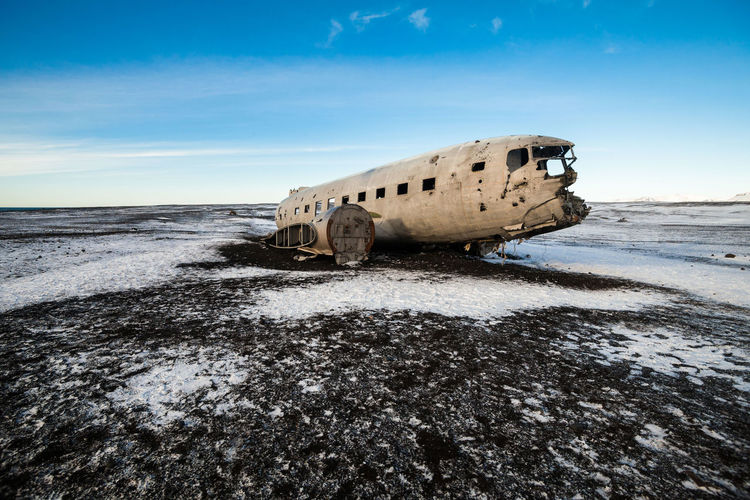 Abandoned airplane on beach during winter
