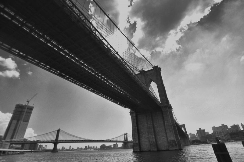 EyeEm Selects Bridge - Man Made Structure Connection Architecture Engineering Built Structure Suspension Bridge Transportation Sky Low Angle View Travel Destinations River Outdoors Travel Cloud - Sky Day Bridge Water Brooklyn Bridge / New York Manhattan Bridge No People Black And White Friday