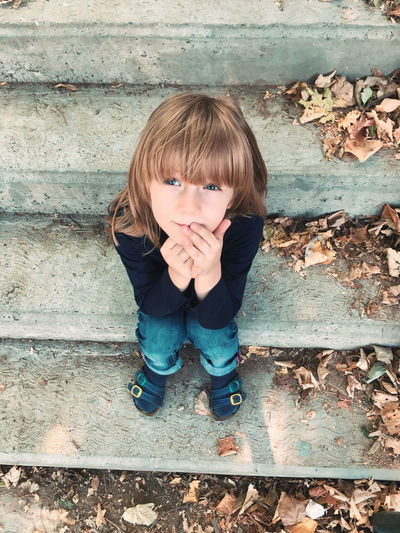 Smiling boy looking away while sitting on staircase