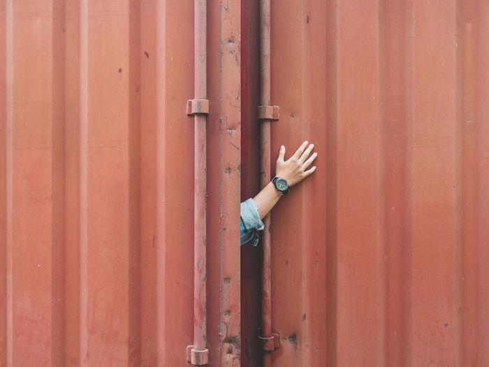 Close-up of human hand by metal door