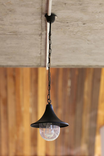 Close-up of light bulb hanging on wall