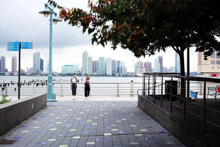 People on footpath in city against sky
