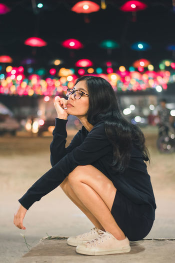 Real People One Person Lifestyles Leisure Activity Young Adult Focus On Foreground Sitting Young Women Illuminated Women Night Side View Three Quarter Length Adult Looking Holding Casual Clothing Hairstyle Beautiful Woman