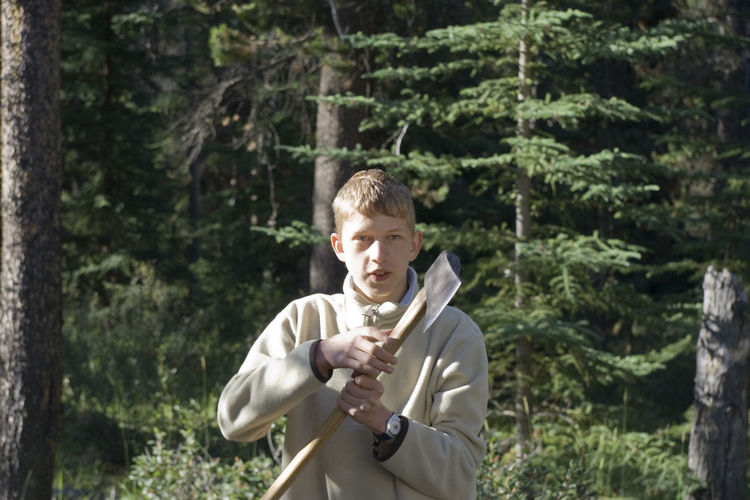 teenage boy holding an axe - wood-chopping in jasper national park, canadian rockies Adolescence  Axe Boy Boys Canada Casual Clothing Chopping Coniferous Tree Firewood Forest Front View Holding Masculinity Nature One Boy Only One Teenage Boy Only Outdoor Life Outdoors Scout Standing Strength Survival Teenage Boys Woods Work Tool