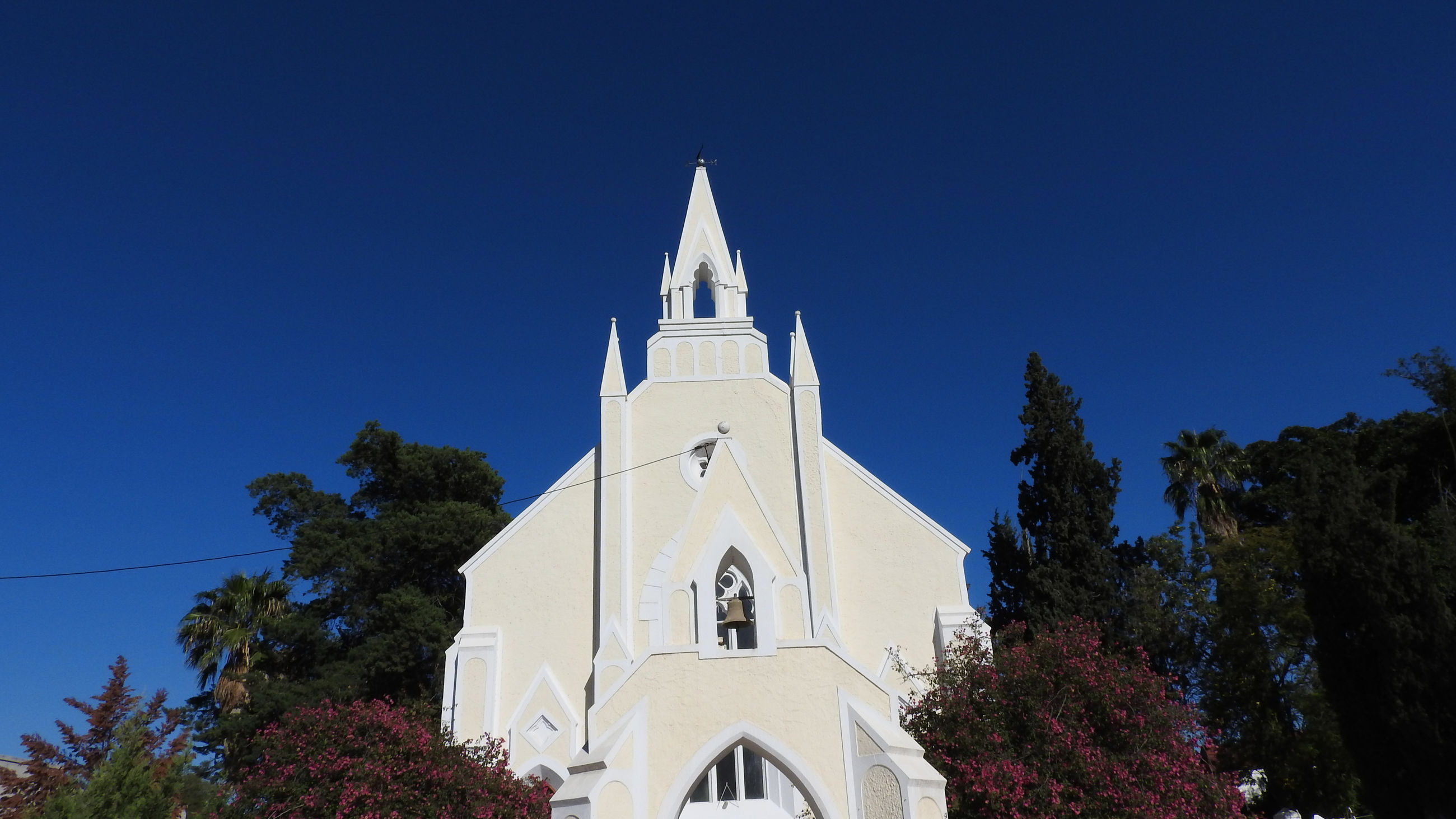 architecture, religion, building exterior, place of worship, built structure, church, spirituality, low angle view, clear sky, tree, blue, outdoors, facade, day, high section, exterior, bell tower, steeple, no people