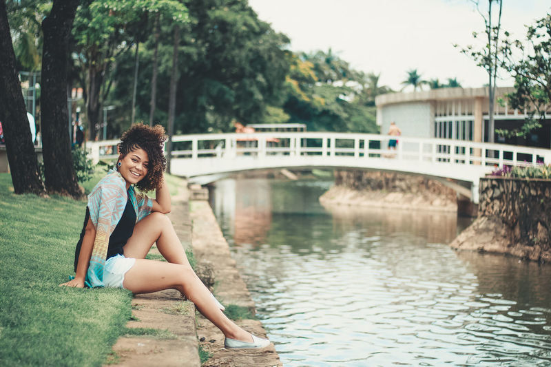 Portrait of young woman sitting by canal against trees and bridge