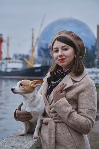 Portrait of smiling young woman with dog standing outdoors