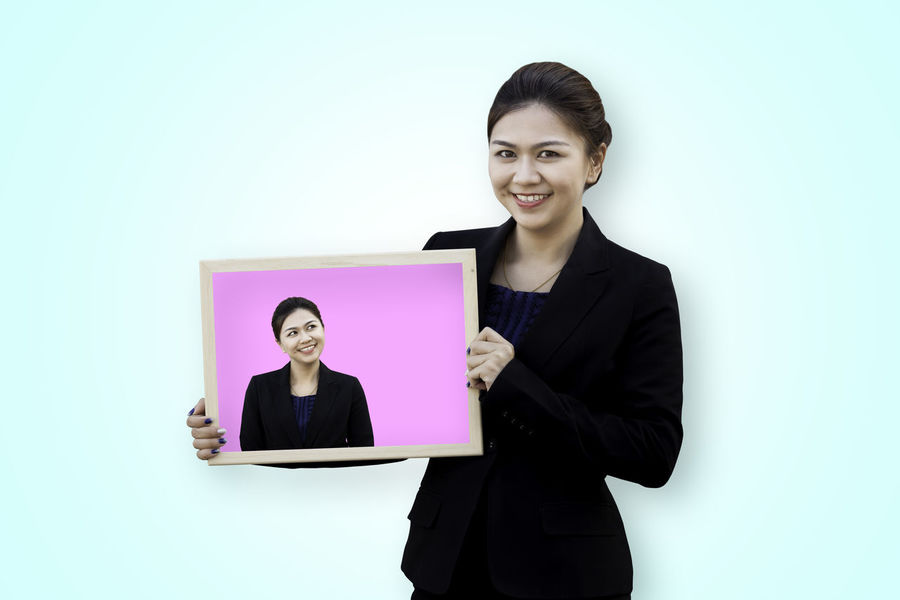 Asian business woman holding her self in white board Asian  Isolated Poster Thai Thinking Advertisement Billboard Blended Images Board Business Businesswoman Colored Background Concept Confidence  Hand Holding Looking At Camera People Portrait Showing Smiling Studio Shot Suit Waist Up Young Women