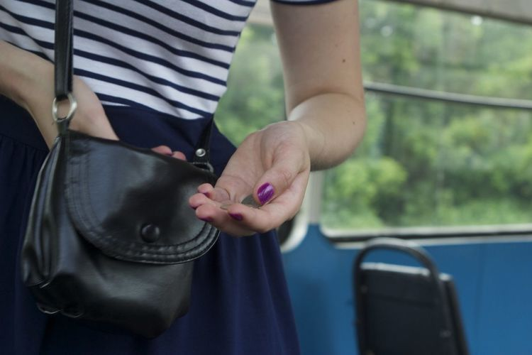 Midsection of woman picking coins from purse