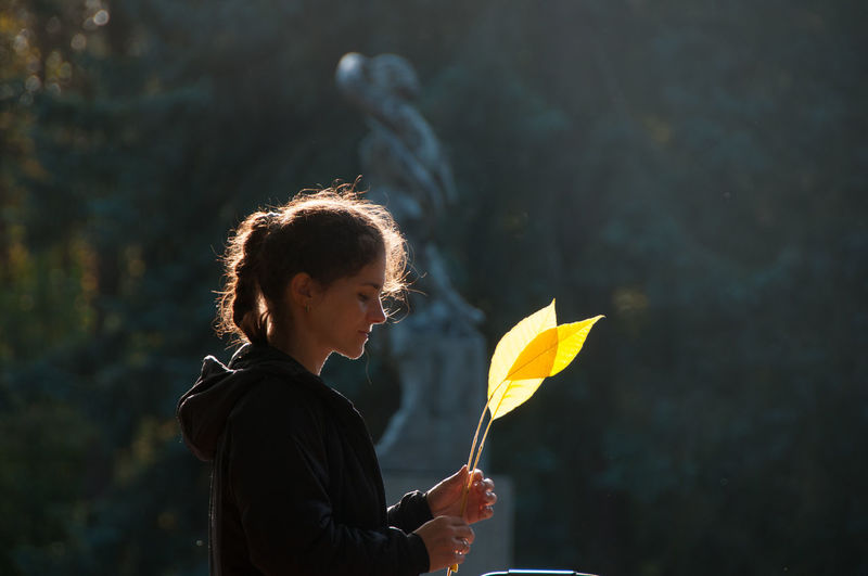 Portrait of woman holding yellow leaf