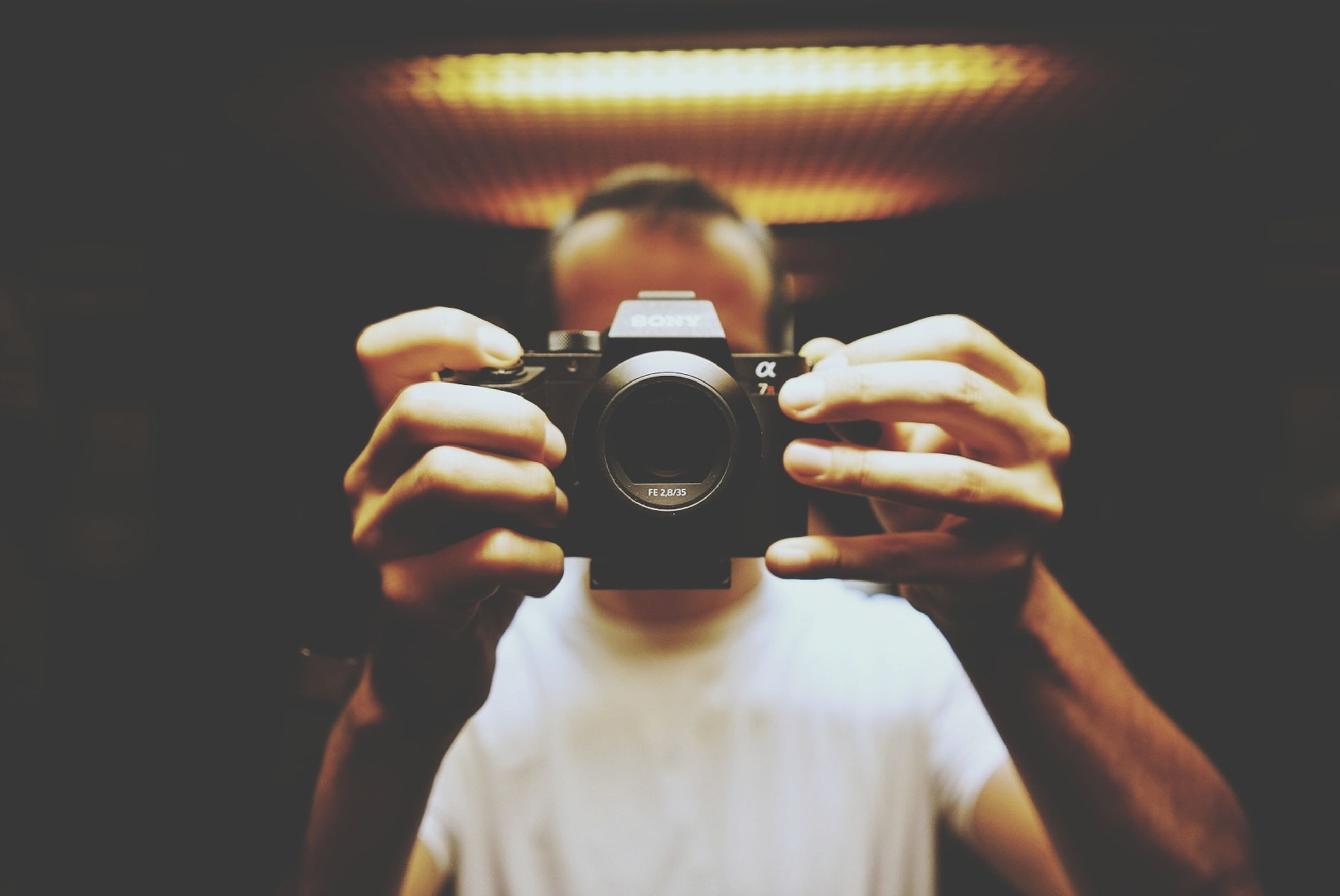 camera - photographic equipment, photography themes, one person, photographing, front view, photographic equipment, holding, occupation, technology, activity, indoors, real people, focus on foreground, headshot, portrait, camera, photographer, digital camera, lifestyles, modern, slr camera