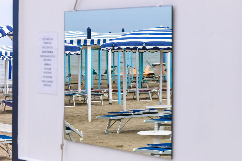 Beach in the reflection of the mirror, Italy, Riccione Deck Chair Italy. Riccione Mirror Reflection Vacations Wall Beach Blue Chair Day Empty Italy No People Resort Rest Sand Sky Summer Umbrella