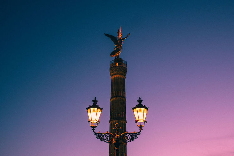 Low angle view of statue on column against sky during sunset